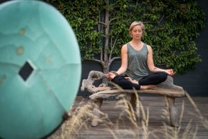 Lisa Meditating in front of green sculpture at Samadhi
